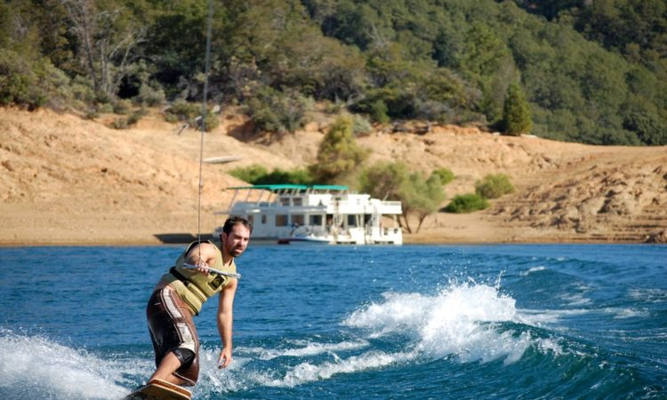 Man wakeboarding with houseboat in the background