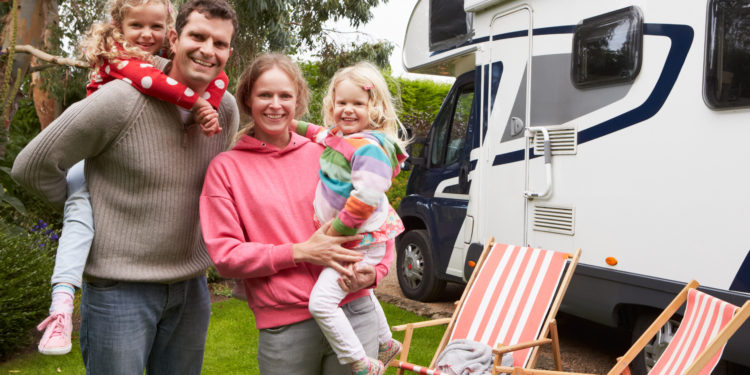 Family of 4 standing by RV in campground