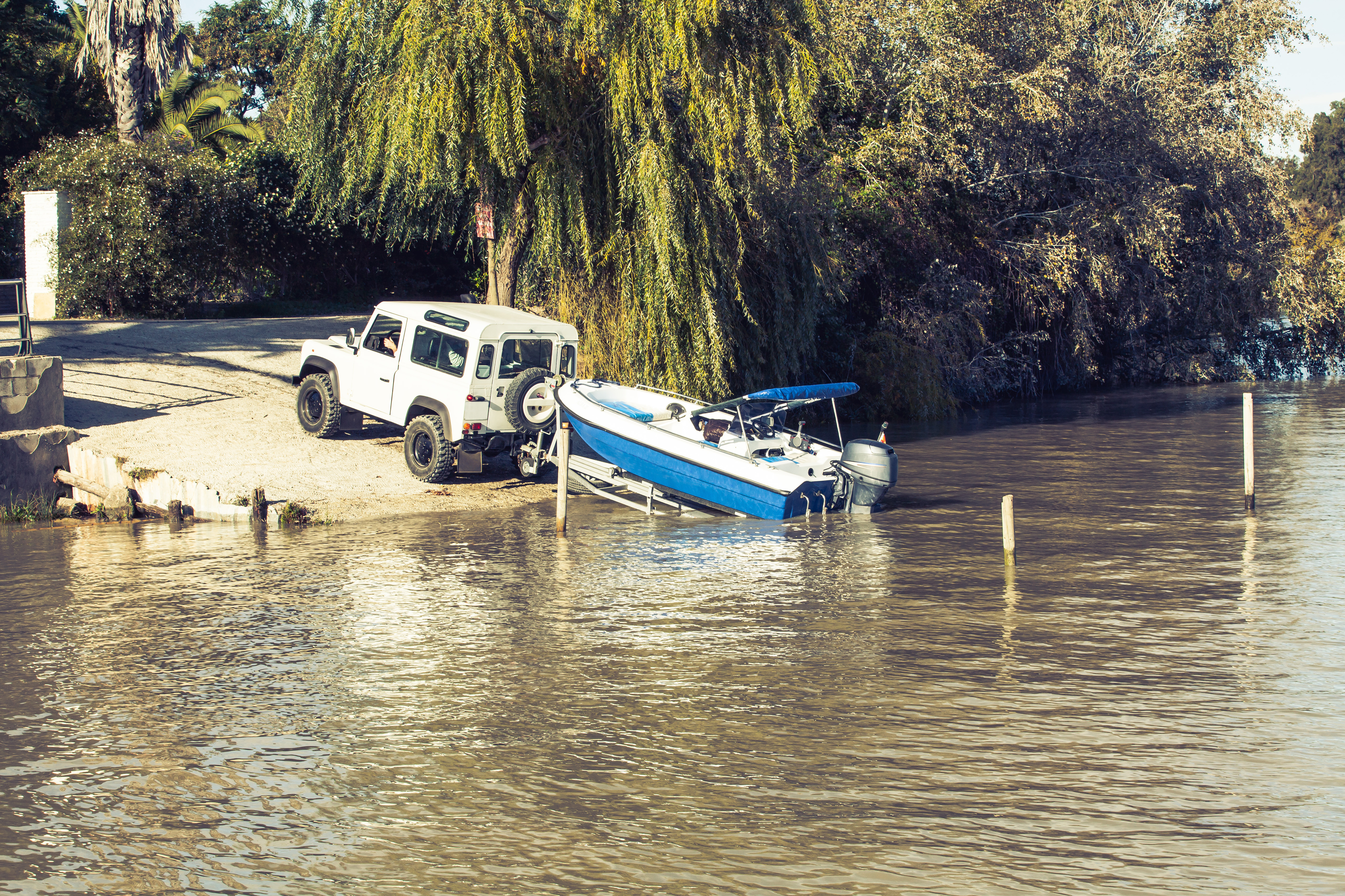 All terrain vehicle towing a trailer with a boat on top into the water.