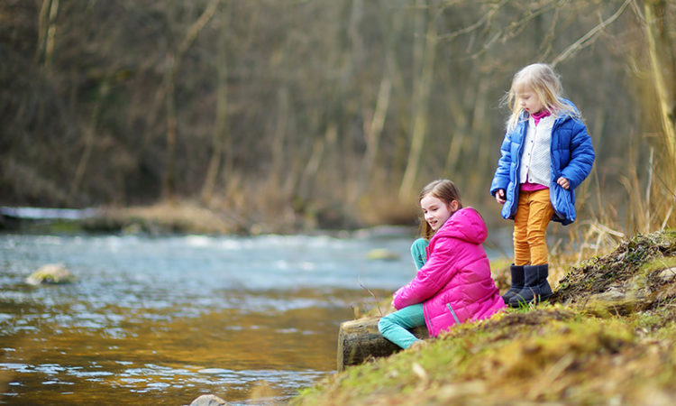 Two cute little sisters having fun by a river on warm spring day
