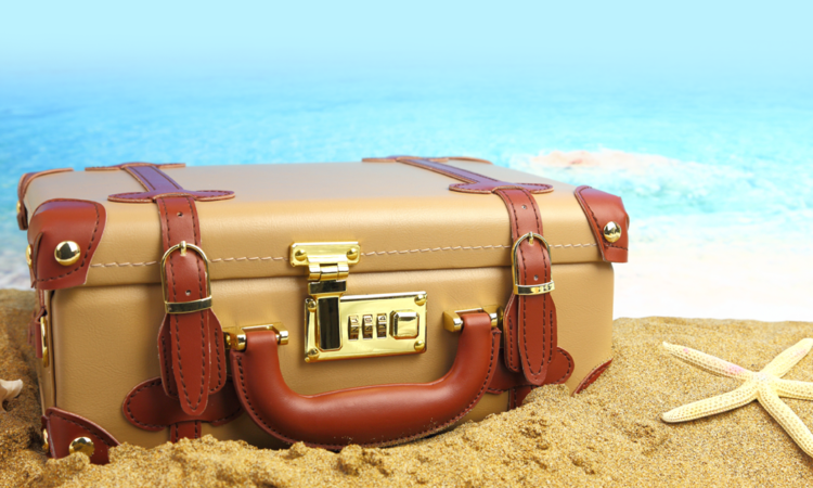 vacation_suitcase on sand beside water