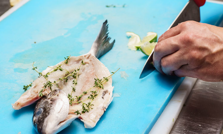 hands prep fish on houseboat counter
