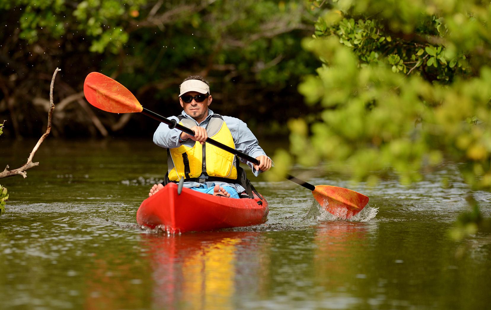 man paddling kayak during houseboat rentals