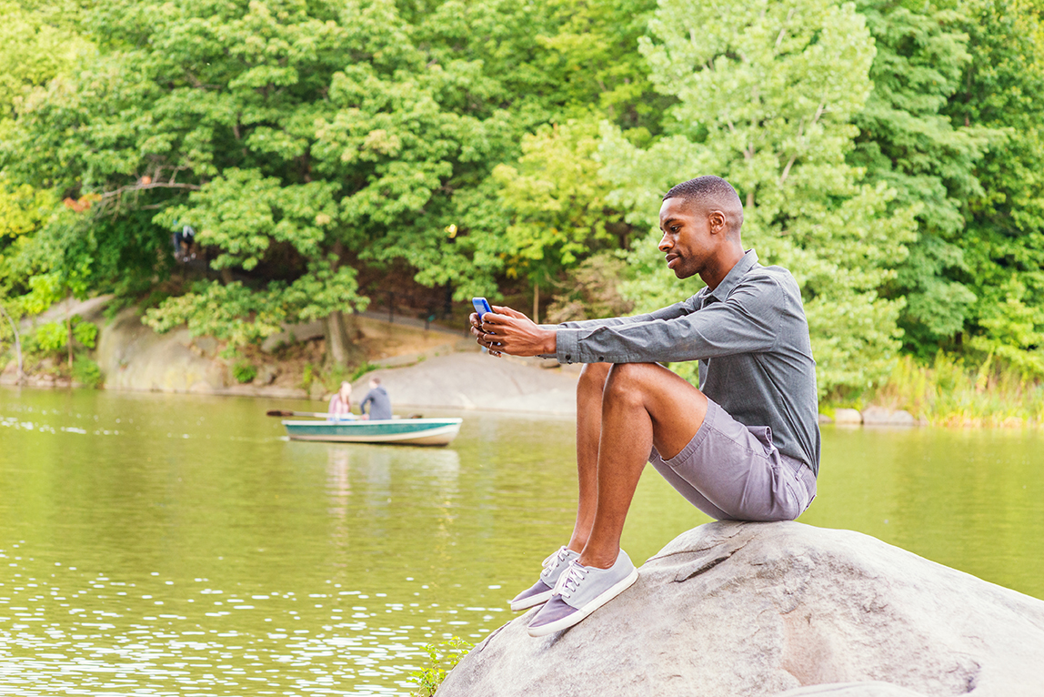 man waiting learning about houseboat rentals on tablet